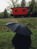 Person under an Umbrella Looking at a Parked Train Caboose