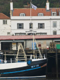 Fishing Boats in Whitby Harbour with Famous Magpie Cafe in Background  Yorkshire  England