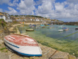 Small Unturned Boat on Quay and Small Boats in Enclosed Harbour at Mousehole  Cornwall  England
