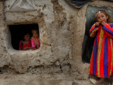 Displaced Girls Smile as They Look Out from a Shanty, in a Refugee Camp in Kabul, Afghanistan Papier Photo
