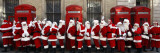 Men from the London Santa School  Dressed in Christmas Outfits  Pose by Telephone Boxes in London
