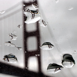 Rain Drops are Shown on a Car Windshield with the Golden Gate Bridge in Background