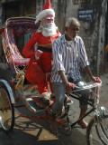Indian Trishaw Driver Takes a Statue of Santa Claus to a Shop for Christmas Decoration in Agartala