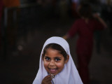 Pakistani Girl Waits for Her Mother to Get Rice During a Donated Food Distribution at the Beri Iman