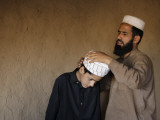 Afghan Refugee Teacher Adjusts the Turban for His Student