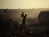 Displaced Man Holds His Baby Next to His Tent in Jalozai Refugee Camp Near Peshawar  Pakistan