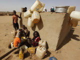 Refugee Children Wait their Turn to Collect Water Supplies at a Water Station in Sudan