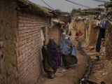 Three Afghan Refugee Women and their Children Walk in an Alley of a Poor Neighborhood in Pakistan