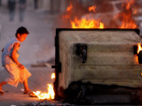 Bahraini Child Plays Near to Burning Tires and a Dumpster