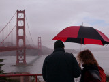 Tourists Use an Umbrella During a Light Rain  Looking at the Golden Gate Bridge in San Francisco