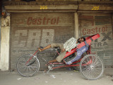 Indian Rickshaw Puller Rests in the Shade at a Closed Market Complex in New Delhi  India