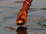 Woman Praying on the Banks of the River Ganges Fills Water into a Copper Vessel for a Ritual