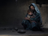 Sarab Village Resident Comforts Her Son after Having Early Morning Opium Smoke with Family Members