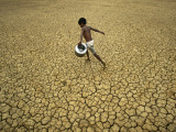 Indian Village Boy Runs Through a Parched Field on World Water Day in Berhampur  India