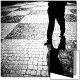 Silhouette of Mans Legs Walking on Cobblestone Street at Night