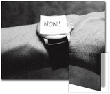 The Word Now as a Reminder Attached to a Watch on a Male Arm