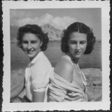 Two Women Friends Sitting Back to Back on a Beach in Italy