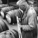 Customs Official Checks the Volume of Wine in a Barrel