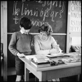 A Boy Pupil Reading with His Teacher  at Her Desk in Front of the Blackboard
