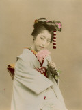 A Japanese Girl in Traditional Costume and Elaborate Hairstyle Smelling a Pink Flower