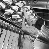 Factory Employee Checks Large Spinning Machine