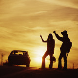 Silhouetted Couple Hitchhiking on Roadside