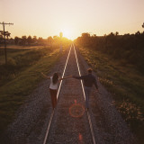 Couple Walking on Railroad Tracks Holding Hands