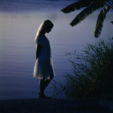 Silhouette of woman standing near a lake