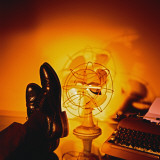Feet Resting on Desk with Vintage Fan and Typewriter