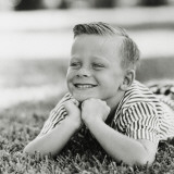 Portrait of Boy with Freckles Smiling on Grass