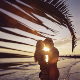Couple Embracing Next to Palm Tree at Sunset