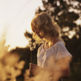 Woman Holding Flower Outdoors at Dusk