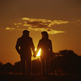 Couple Walking Holding Hands at Sunset