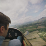 Man in Airplane Cockpit Looking Out at Fields Below