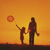 Mother and Daughter Walking at Sunset Holding Balloon