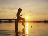 Boy Sitting on Pier Fishing at Sunset