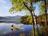 Man Paddles Canoe on Autumn Day
