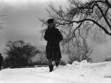 Woman in Winter Clothing Running Through Snow