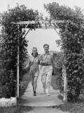 Couple Walking on Footpath Towards Rose Covered Pergola