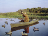 Hunter Sitting in Canoe Surrounded by Duck Decoys