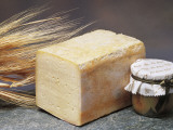 Close-Up of Cheese (Tilsit Cheese) with Wheat and a Covered Jar