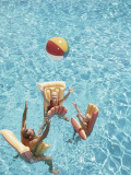 Family Tossing Beach Ball While Floating on Pool Rafts