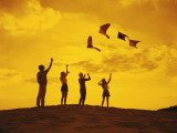 Friends flying kites on a hill at sunset