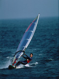 Man Glides the Waves While Windsurfing