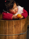 China  Anhui Province  Child Sits in Bucket Warmed by Charcoal