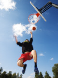 Low Angle View of a Basketball Player Slam Dunking