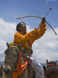 China  Western Sichuan Province  Litang  Tibetan Man Performing Archery on Horseback at Horse Race