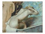 Femme assise sur le rebord d' une baignoire et s'épongeant le cou