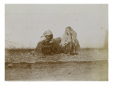 Two Men Leaning Against a Wall in a Street of Biskra