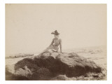 Jeune femme assise sur un rocher  au bord de la mer